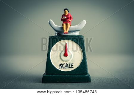 Miniature doll woman who are riding the scale