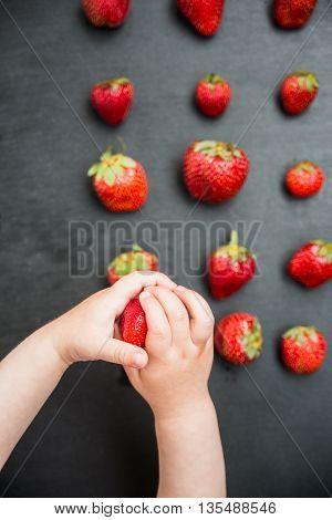 child picks strawberries on black desk background