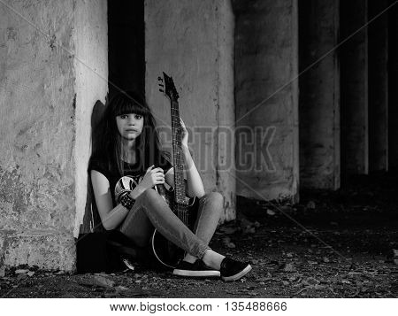 Beautiful young girl playing the guitar on the ruins