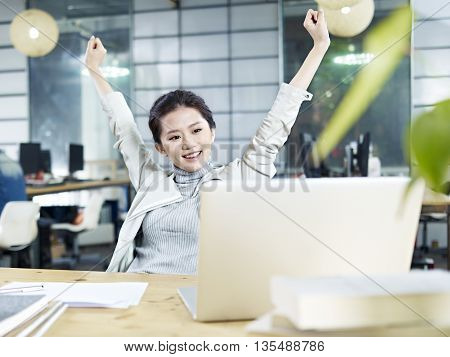 young asian business woman celebrating with arms raised in office.