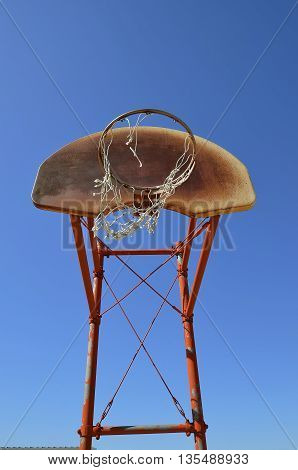 An outdoor basketball backboard is full of rust and holds a ripped net.