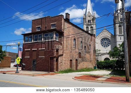 JOLIET, ILLINOIS / UNITED STATES - JUNE 1, 2015: An old brick building stands across the street from the historic Saint Joseph Catholic Church in downtown Joliet.