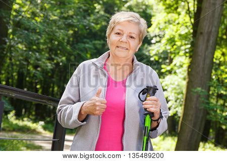 Elderly Senior Woman Holding Nordic Walking Sticks And Showing Thumbs Up