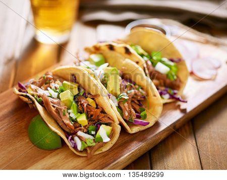 three  pork carnitas street tacos in yellow corn tortilla with avocado, onion, cilantro and cabbage