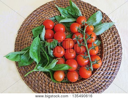 Healthy snack of cherry tomatoes on a stem with fresh basil for vegans
