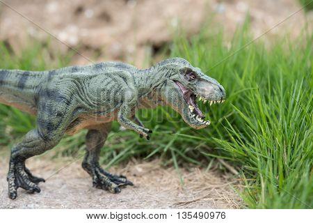 a tyrannosaurus toy next to grass horizontal