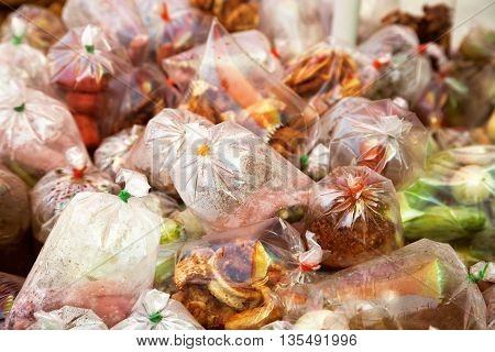 Street food cart with exotic Asian takeaway food in plastic bags. Outdoors food vendor stall on a sidewalk