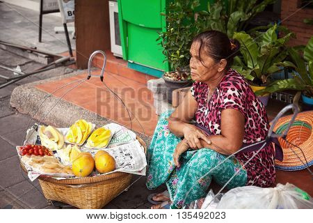 Pattaya Thailand - March 28 2016: Thai street vendor selling fruits from baskets. Food seller sitting on pavement
