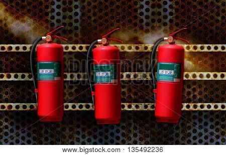 fire extinguisher red tank on grunge steel wall