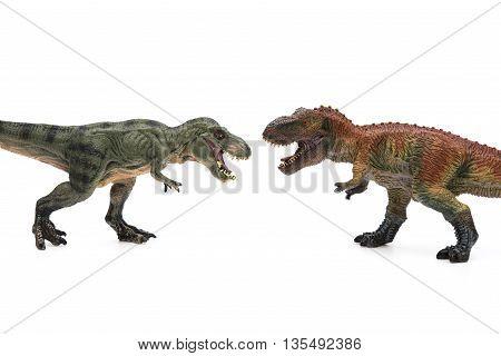 two tyrannosaurus toys on a white background
