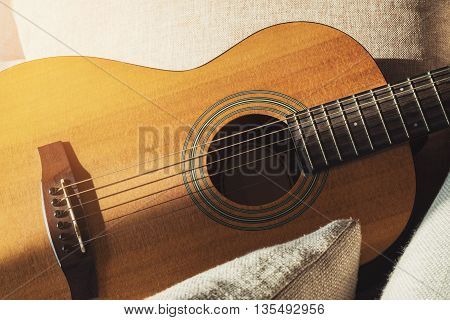 Close-up wooden acoustic guitar on fabric sofa with pillows, vintage tone soft focus