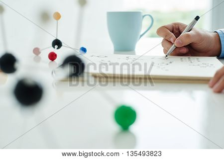 Close-up of researcher writing formulas at the table