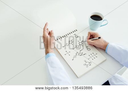 Man working with formula into notebook at table