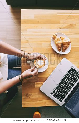 High angle view of woman drinking cappuccino with croissants