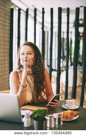 Pensive businesswoman sitting at cafe with laptop and smartphone