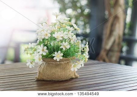 White artificial flowers in mini sack on the table