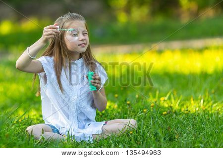 Little girl sitting in the grass and make blowing bubbles.