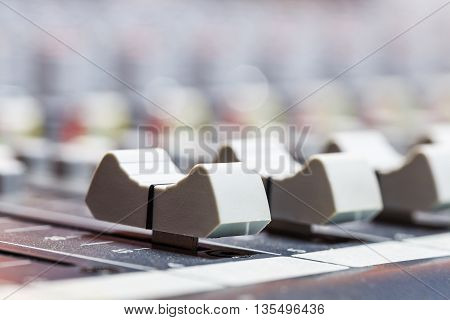 Closeup on sliders of sound mixing console in audio recording studio