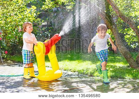 Two funny little brother boys playing together and splashing with a garden hose on hot and sunny summer day. Kids having fun outdoors. Funny outdoors leisure wth water for children.