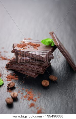 Stack of chocolate chunks with mint on a dark stone background with cocoa closeup