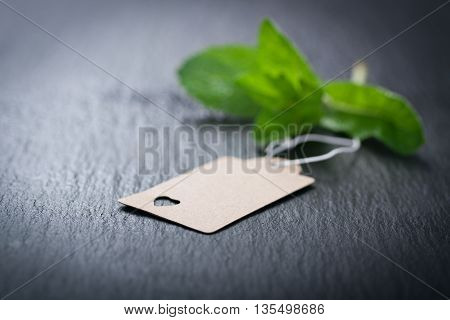 Paper tag with heart on a dark stone background with mint on a background, closeup