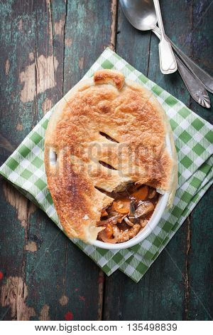 Homemade vegetable pie with tomato sauce and puff pastry in a bowl with red wine, top view