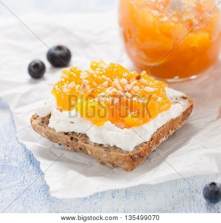 Sandwich with fruit jam and cottage cheese on a wooden background