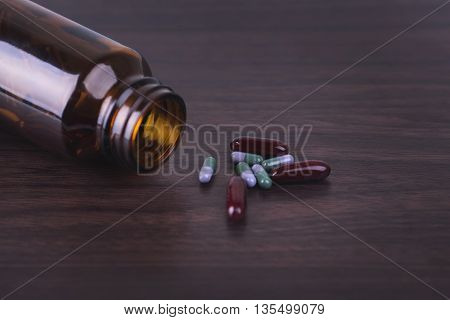 Pill bottle with various pills and capsules on wooden background