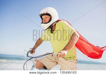 Senior superhero riding bike on the beach