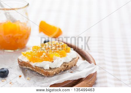 Sandwich with fruit jam and cottage cheese on a board closeup with copy space