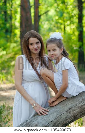 Little girl and her pregnant mother in the forest