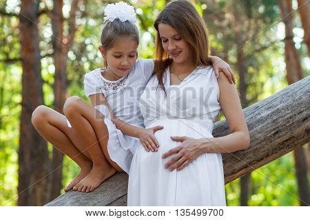 Pregnant woman and her daughter relaxing in the forest
