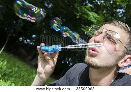 Young bearded man in glasses blowing soap bubbles