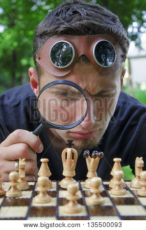 Young man with steam punk glasses looking through magnifying glass at chess board