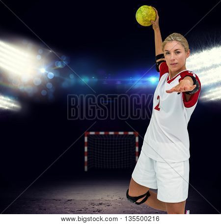 Sportswoman throwing a ball against view of spotlights