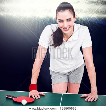 Composite image of female athlete leaning on ping pong table against spotlight