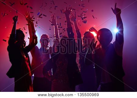 Silhouettes of young people in neon light in confetti