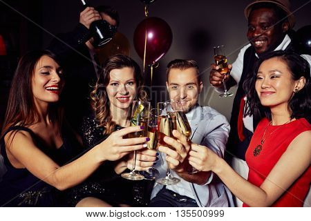 Young friends looking at camera with champagne flutes