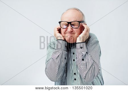 Displeased senior feeling uncomfortable and covering ears