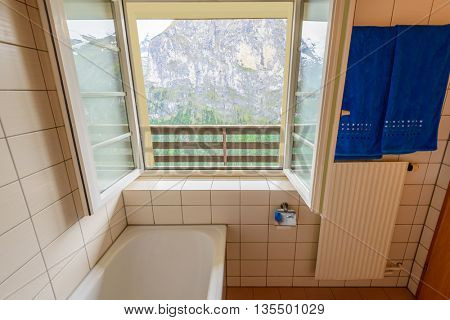 Fragment of a bathroom with window and view at swiss alps mountains.
