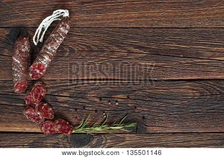 Salami sausages sliced with pepper and rosemary on dark wooden table. Space for text. Top view