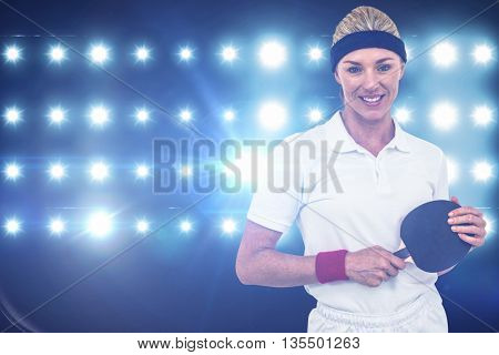 Composite image of female athlete holding a paddle against spotlight