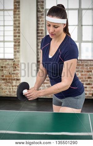 Composite image of female athlete playing table tennis indoor