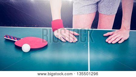 Composite image of female athlete leaning on ping pong table in a stadium
