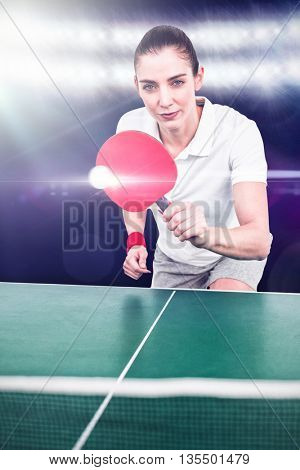 Composite image of female athlete playing ping pong against spotlight