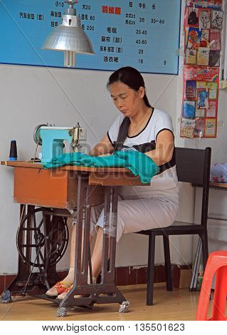 Wuhan, China - June 22, 2015: woman is using a sewing machine outdoor in Wuhan, China