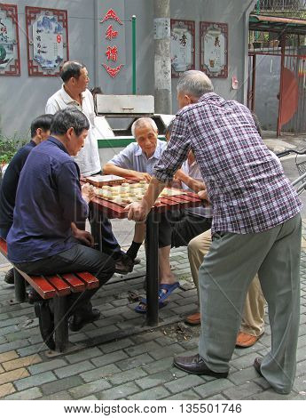 Wuhan, China - June 22, 2015: men are playing board game outdoor in Wuhan, China