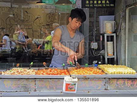 Wuhan, China - June 22, 2015:man is selling snacks outdoor in Wuhan, China