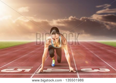 Composite image of sportswoman in the starting block on race track