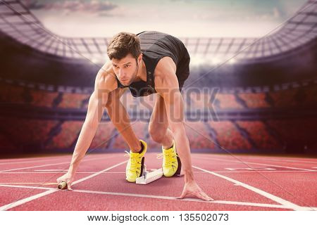 Composite image of sportsman starting to sprint in a stadium